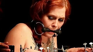 Gagged redhead teen babe in bondage device gets spanked - 6:00